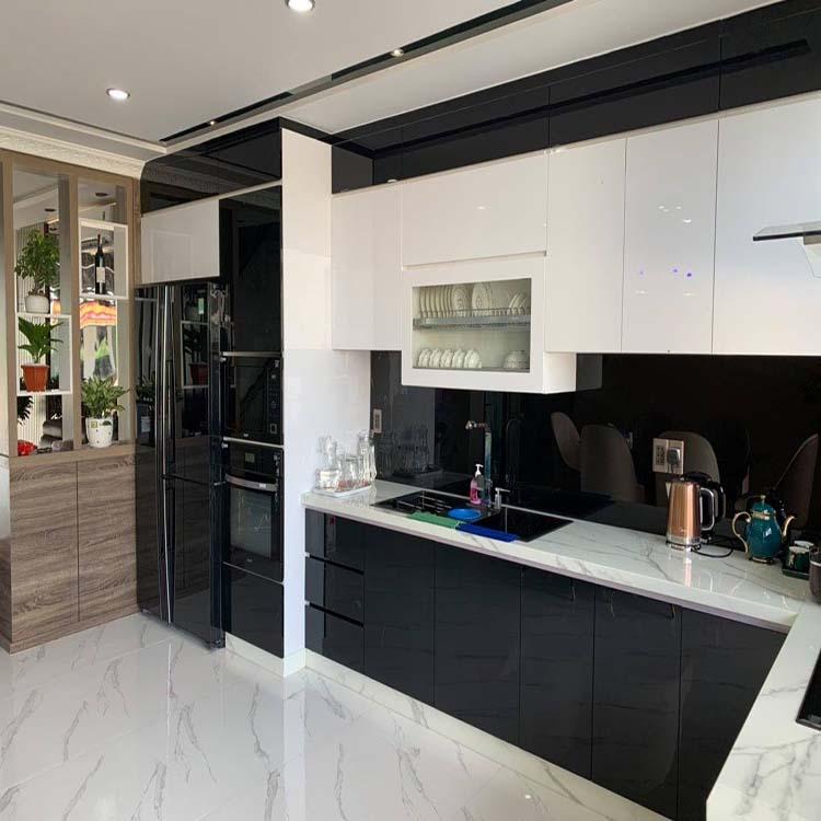Tủ bếp gỗ công nghiệp, kết hợp màu đen và màu trắng phù hợp với lớp nền gạch của căn nhà