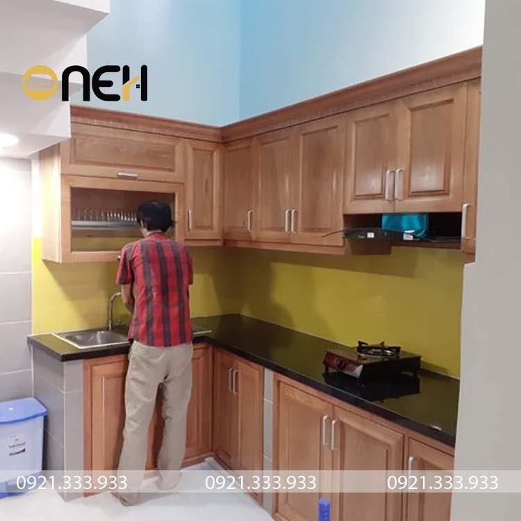 Tủ bếp dưới cánh tủ được làm hoàn toàn bằng gỗ xoan, các tay nắm được sử dụng theo kiểu truyền thống